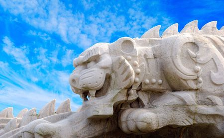 Statue of the tiger against blue sky.