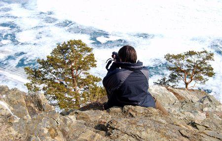 Photographer makes shots of the landscape. Frozen Baikal lake.  photo
