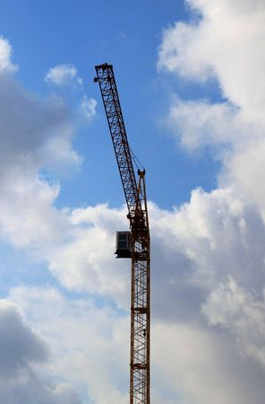 industry moody: Crane against cloudy sky. Front view.