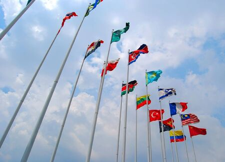 Group of Flags against cloudy sky.  photo