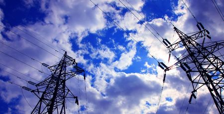 Two electricity pylons against cloudy sky. Day.  photo