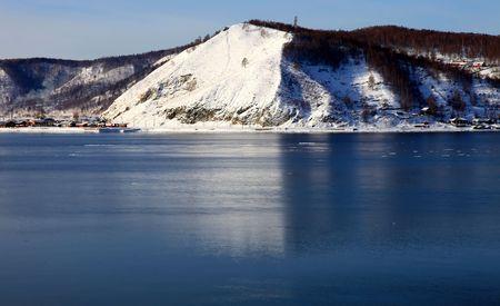 Frozen Lake Baikal. Spring. Day. Mountains on horizon.  photo