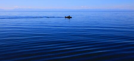 Lake Baikal, summer. Motor boat in middle of the lake.   photo
