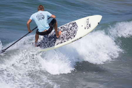 board shorts: Pacific Beach, San Diego Revolt Summer Surf Series 6.0 08172012 - Paddle Boarder Riding Wave