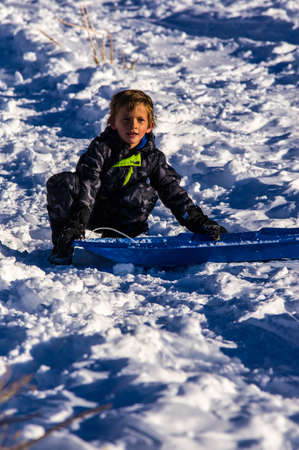 Young Boy Sledding On a Sunny Winter Day