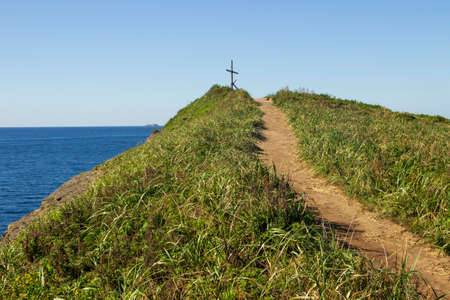 The road leading to the top of the hill near the cliff on the seashore, on which is building an old wooden cross.  Tobizin cape, Russian island, Vladivostok.