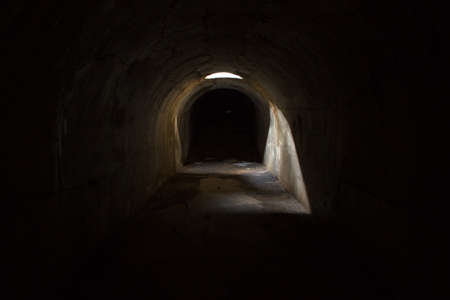 A gloomy dark underground corridor, sealed through a hole in the ceiling at Fort Pospelova on the Russian island in Vladivostok. Standard-Bild