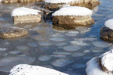 Sea shore in winter, covered with ice and snow. Round ice floes floating in sea water.
