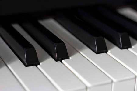Black and white piano keys in dim lighting and shadows.