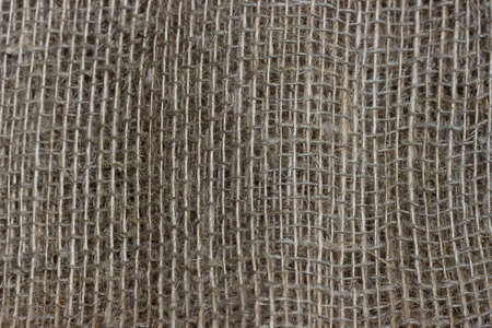 The structure of the threads of a natural burlap fabric close up.