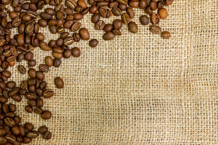 Roasted arabica coffee beans sprinkled on burlap with copy space.