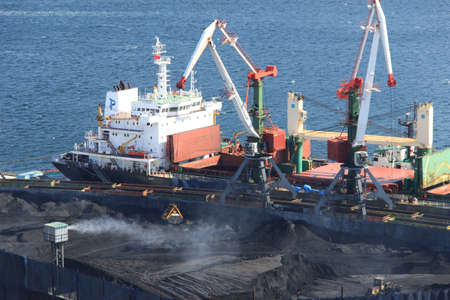 Vladivostok, Russia - October, 5, 2019: Coal transshipment from the railway to the ship in the open-pit coal terminal of the trading port of Vladivostok.