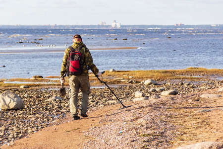 A treasure hunter with a metal detector walks along the sandy deserted beach in search of lost coins and jewelry.