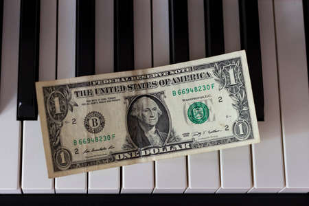 One dollar banknote lying on the piano keys. The dollar as a symbol of global economic management.