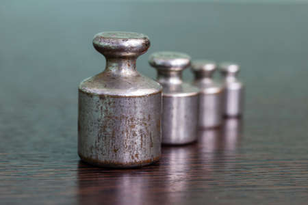 A set of old scratched iron weights for a pharmacy scale.