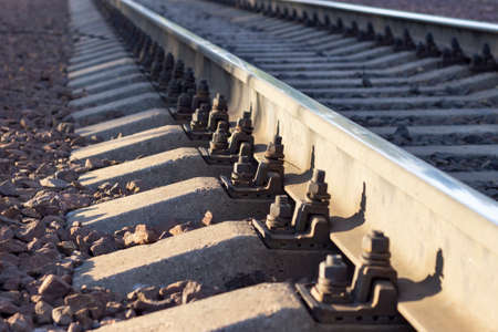 Close-up of iron bolts securing rails to concrete sleepers.