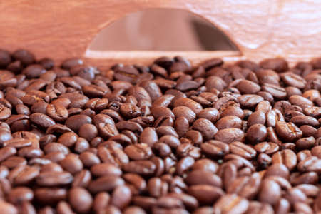 A wooden box full of roasted coffee beans.