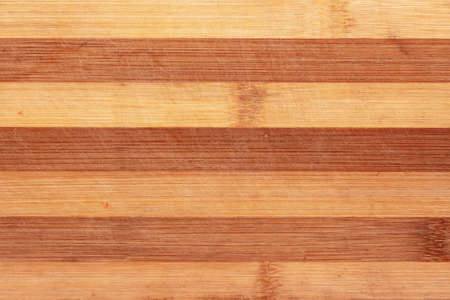 Surface of a striped wooden scratched kitchen chopping board.