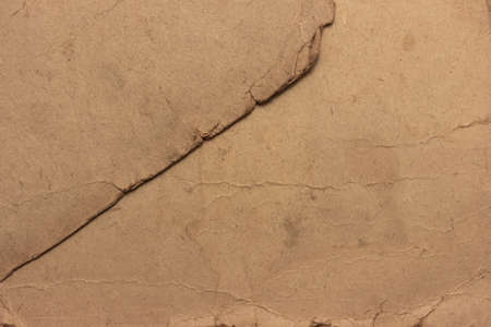 The texture of old stained, faded cardboard. Cardboard sheet with torn, frayed edges.