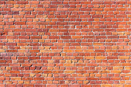 A wall of old, cracked bricks, with a weathered and faded surface. Restored brickwork of an old house. Standard-Bild