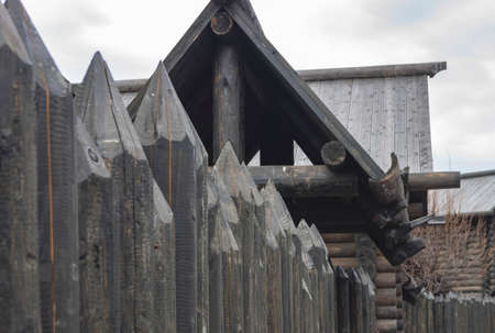 A protective palisade around a wooden log house in a Russian village. Traditional Russian construction of huts.