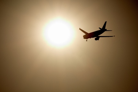 Commercial airplane flying towards the sun photo