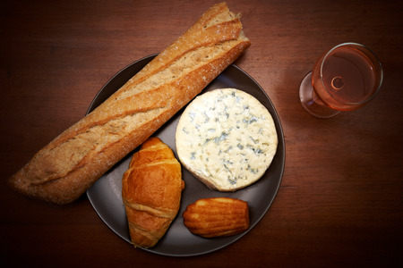 French blue cheese, baguette, croissant, madeleine and glass of wine on a table photo