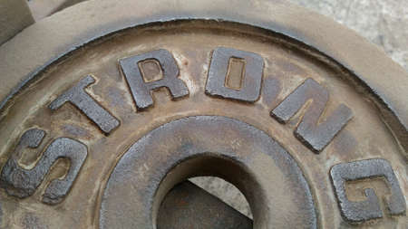 corrode: The Sheet metal with letters STRONG that are polisheding rust off.polisheding Rust hen some. Stock Photo