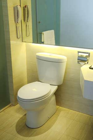 Toilet in yellow bathroom with linoleum floor photo