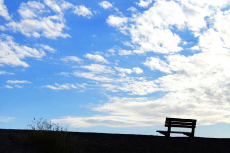 empty chair: Empty chair silhouette under blue sky