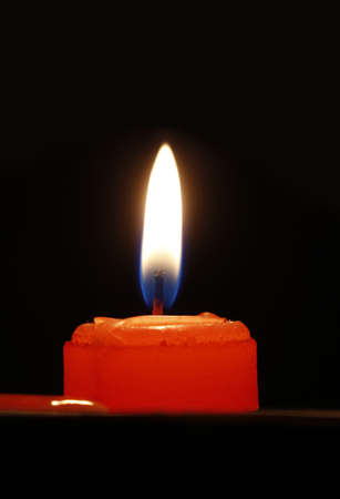 dazzling: Red candle, on a black background, dazzling flashing light  Stock Photo