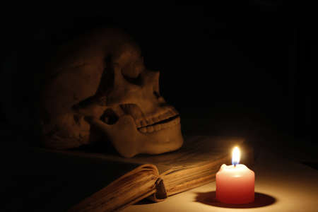 Halloween images, burning candles in an ancient skull and book  photo