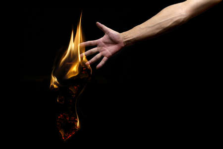 Black background, men arm, burning into ashes heart, lost love from my hands, desperate parting Stock Photo