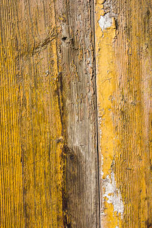 mottled: Yellow mottled paint weathering cracked wooden close-up Stock Photo