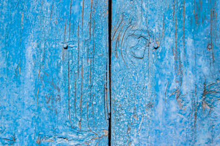 mottled: The blue color paint mottled weathering cracked wooden doors