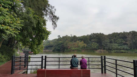 backview: old couple sitting beside to each other