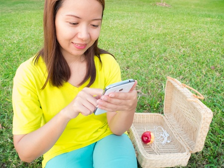 asia beauty woman play a smartphone in the park photo