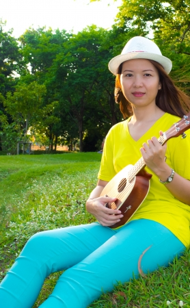 asia beauty woman play ukulele in the park photo