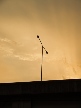 a streetlamp silhouette on the motorway at sunset photo