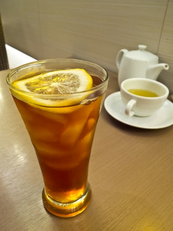 lemon ice tea and green tea in white cup and white teapot on the wood table photo