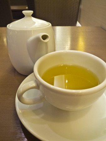green tea in white cup and teapot photo
