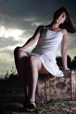 beauty girl sitting on suitcase photo
