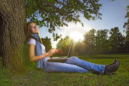 young beauty girl with laptop in park photo