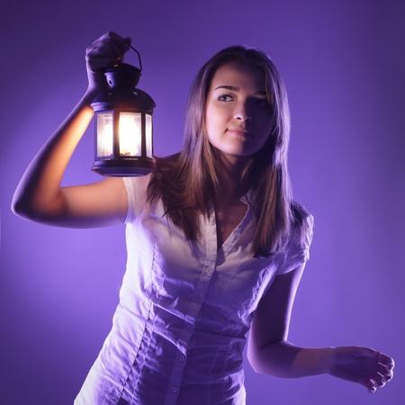 beautiful girl with lantern seeking in night photo