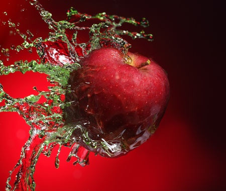 red apple in juice stream photo