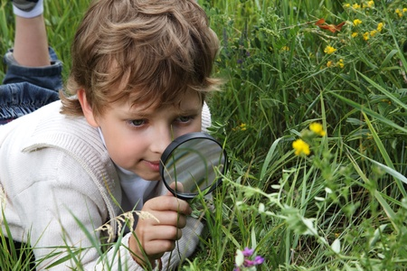 explore: boy with magnifying glass outdoors Stock Photo
