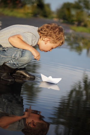 boy blow on paper ship photo