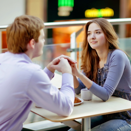 two friends talking: young couple in cafe