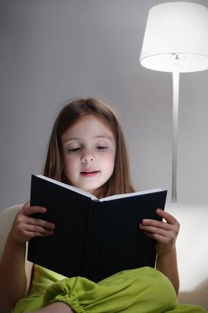 leyendo la biblia: chica de belleza leer el libro en el sof� Foto de archivo