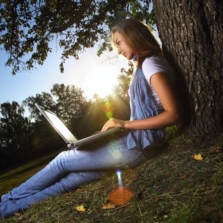 lens flare: young beauty girl with laptop in park, photo with artistic lens flare effect
